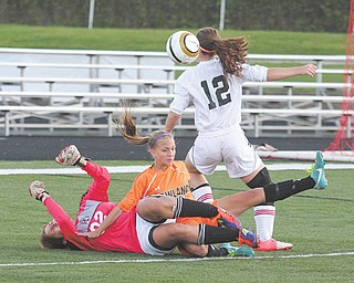 Canfi eld goalie Victoria Villano (02) and Howland's Jordan Entler, middle, get tangled up as Canfield's Sophia Mancini (12) tries to get control of the ball during the first half of Monday's game at Canfield High School.