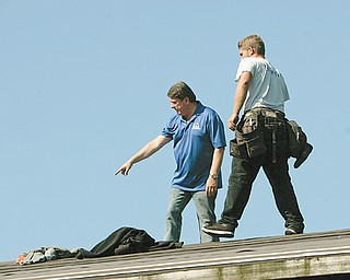 Sam Boak, of Boak & Sons Inc., inspects the roof of a Zander Drive home with Jason Brinsey of Boardman. Boak's company is one of the main donors for an HBA community project to remodel the home.