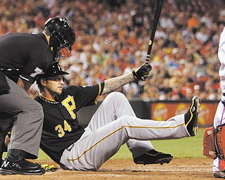 Home plate umpire Manny Gonzalez tries to help the Pirates' A.J. Burnett up after Burnett fell to the ground after striking out with the bases loaded in the fourth inning of Wednesday's baseball game against the Cincinnati Reds in Cincinnati. The Pirates fell to the Reds, 2-1.