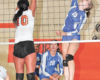 Jackson-Milton's Erica Hughes (19) spikes the ball over Howland's Megan Papalas (10) for a winner during Monday's third game at Howland High School. The Bluejays won in three games.