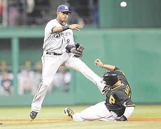 Milwaukee Brewers shortstop Jean Segura, left, throws to first after forcing out Pittsburgh Pirates' Jose Tabata on the front end of a double play that Andrew McCutchen hit into during the first inning of a game in Pittsburgh on Tuesday.