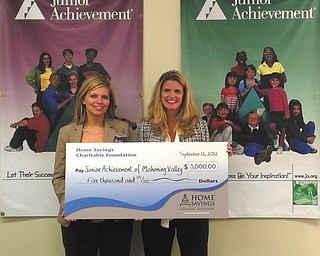 Mindy Wiesensee of Home Savings McCartney office, left, and Michele Merkel, president of Junior Achievement of Mahoning Valley, hold an oversized check for $5,000. Home Savings Charitable Foundation recently made the donation to Junior Achievement. JA volunteers teach young people in kindergarten through 12th grades about entrepreneurship. JAMV was formed in 1992 with the consolidation of JA of Trumbull County established in 1952, and JA of Youngstown Area established in 1953.  JAMV coordinates programs in Mahoning, Trumbull, Columbiana and Ashtabula counties.