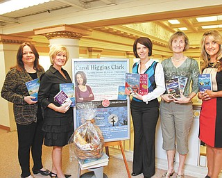 Books by Carol Higgins Clark, featured guest at the Public Library of Youngstown & Mahoning County's Literary Society Author Event, are shown by, from left, Janet Loew, communications and public direcctor at the library; Phyllis Bacon, Crissi Jenkins and Karla Edwards, members of the Literary Society; and Deborah Liptak, library development director. The author event will be Oct. 11 at the main library in Youngstown. Photo by: ROBERT K. YOSAY  | THE VINDICATOR