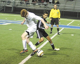 Canfield's Kasey Montezari, right, and Poland's Scott Marucci battle for control of the ball during an All-American Conference American Division soccer match Thursday night in Poland. The Cardinals controlled the Bulldogs, 6-1.