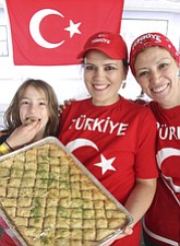 Gulay Yazar of Canfield, center, her daughter, Edanur, 9, and sister, Nurten Toslu of Philadelphia, baked the baklava and grape leaves sold at the Turkish booth at the Arab-American Festival of Youngstown Saturday.
