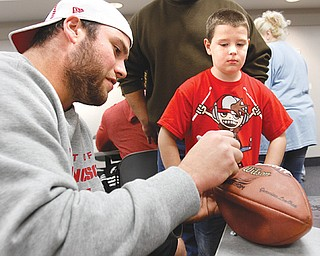 Stevie Pateras, 8, of Austintown gets a signature on his football from 49ers offensive lineman Al Netter.