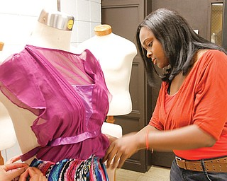 Youngstown State University sophomore Naomi Smith of Youngstown works on a dress in preparation for Youngstown Fashion Week. The event this weekend aims to draw attention to the area's fashion stores and designers.