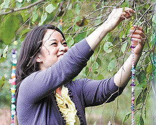 Jess Briganti of Youngstown hangs strands of beads from trees at Mill Creek MetroParks' Fellows Riverside Gardens.
