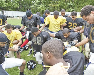 Youngstown Christian School players join in prayer before practice at Ipe Field.