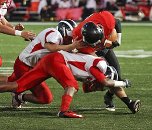 ROBERT  K.  YOSAY  | THE VINDICATOR --..Canfields #21 Conner Kesner  - is tied up after making a first down in first qquarter action - as he is brought down by Niles #60  Nick Lardas and #24  Chris Hillier  ..-Niles at Canfield - Bob Dove Field ..(AP Photo/The Vindicator, Robert K. Yosay)