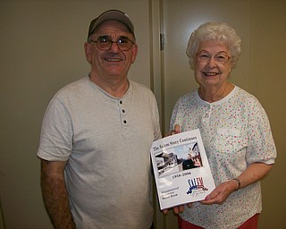 """Joan Lora, above, welcomed 43 new members to celebrate the society's 65th anniversary. With her is Lou Raneri, receiving a copy of the """"The Salem Story Continues, 1956-2006"""" for himself and his wife, Diane. As an all-volunteer organization, members encourage the preservation of the city's history; collect, preserve and exhibit artifacts and memorabilia; and operate the public museum. For information on how to join, contact 330-337-8514 or visit www.salemhistoricalsociety.org."""