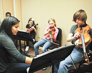 Gia DeAscentis, a Youngstown State University student, teaches a music class to Garfield Johnson, left, Ava Tovarnak, Alanna Clapp and Nathan Clapp at the SMARTS Center.