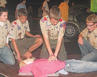 Members of Boy Scout Troop 60, from left, Nick Leonard, Nick Long and Kevin McNally observe as Quinton Currie performs CPR on a fake injured victim Tuesday. The scouts were participating in an emergency preparedness drill to learn first aid.