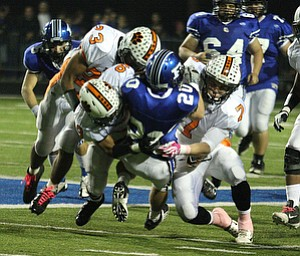 NICK MAYS l THE VINDICATOR  (20) Ross Gould of Poland is tackled by (23) T.K. Fortson, (7) Chris Maze and Trey Bryarly of Howland during thier game Friday night in Poland. howland vs poland 10052012 Poland, Ohio