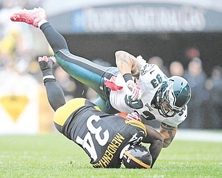 Philadelphia Eagles DE Jason Babin (93) tumbles over Pittsburgh Steelers RB Rashard Mendenhall (34)  as he tackles him after a long run in the first quarter of Sunday's NFL game in Pittsburgh. Mendenhall, making his return from ACL surgery, finished with 81 rushing yards and a score while adding 20 receiving yards. The Steelers edged the Eagles, 16-14 when kicker Shaun Suisham drilled a 34-yard field goal as time expired.