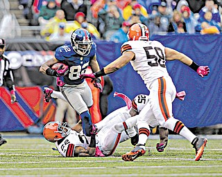 Cleveland Browns defensive back Buster Skrine (22), running back Chris Ogbonnaya (25) and linebacker L.J. Fort try to stop New York Giants wide receiver Rueben Randle (82) as he carries the ball during the first half of an NFL game Sunday in East Rutherford, N.J. The Giants won 41-27.