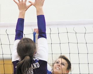 Jackson-Milton senior volleyball player Rachael Obradovich, right, sends the ball over the net as Heartland Christian's Kristin Osborn prepares to defend in Monday's match in North Jackson.