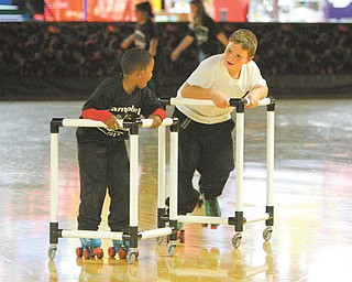 Jawaylyn Bankston, left, and Shawn Paul Joseph take it easy as novice skaters. They were at the Skate Zone in Austintown on Wednesday as a reward for passing their math and reading Ohio Achievement Assessment tests last year.
