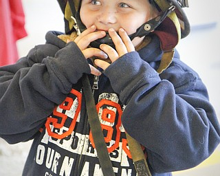 MADELYN P. HASTINGS   THE VINDICATOR  Justin Bish, 5, from Hubbard, Ohio wears his uncle's firefighting helmet at the Hubbard fire open house on October 11, 2012.