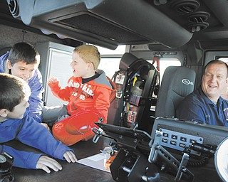 From left, Benjamin Wilcox, 7, Josh Wilcox, 10, Eli Barr, 5, and firefighter Eric Barr, all from Hubbard, enjoy the inside of a fire engine at the Eagle Joint Fire District and Hubbard Volunteer Fire Department's open house. The truck was one of four engines that children and families could see during Thursday's event.