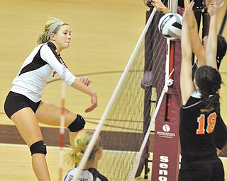 Boardman's Megan Volosin, left, spikes the ball as Howland's Olivia Goodman (18) tries to make a block at the net Tuesday night. The Spartans swept the Tigers in three games in a first-round sectional match at tow-Munroe Falls High School.