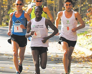 Julius Bor of Erie, Pa., (4) leads a group of runner through Mill Creek Park during the middle leg of the 10K race during the 38th annual Peace Race on Sunday. Bor broke out early and held off Aiman Scullian of Kent to win with a time of 29:54.2.