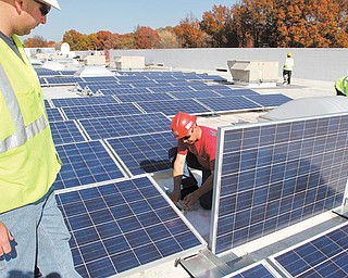 Steve Fife, job foreman from Joe Dickey Electric, works on one of nearly 2,000 solar panels being installed on the roof of the Walmart in Liberty Township as Matt Giles, project manager from The Romanoff Group, looks on.