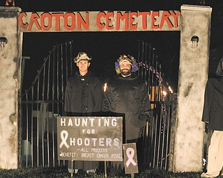 """Bryan Sizer, left, and Thomas Fee of New Castle, Pa., stand before the gates of the Croton Cemetery. The """"cemetery"""" is an elaborate Halloween display the two friends operate to raise money for breast-cancer education and research. It's open every night through Oct. 31."""