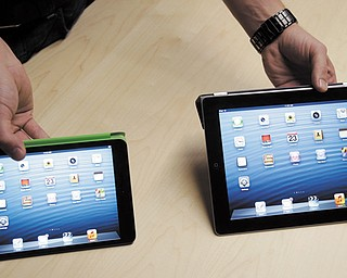 The iPad Mini, at left, is shown next to the 4th Generation iPad in San Jose, Calif. On Tuesday, Apple Inc. revealed the iPad Mini, with a screen that's about two-thirds the size of the full-size model, and said it will cost $329 and up.
