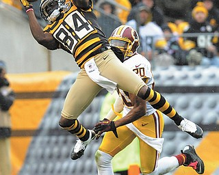 Steelers wide receiver Antonio Brown (84) catches the ball in front of Redskins defensive back Cedric Griffin (20) during the second quarter of Sunday's NFL game in Pittsburgh. Pittsburgh, sporting throwback jerseys from the 1930s, won downed Washington, 27-12.