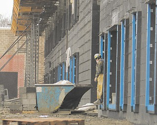 Construction crews work on the Austintown school district's new elementary school buildings Monday. The buildings are scheduled for completion in August 2013, and in preparation, Austintown Township has begun