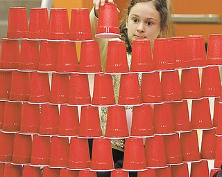 Addison Fonderlin, a second-grader at Hilltop Elementary in Canfield, works on building the tallest plastic-cup tower. Addison and her class participated Thursday in STEM Week at the school for the second year in a row, which consists of science, technology, engineering and math experiments for students to test.
