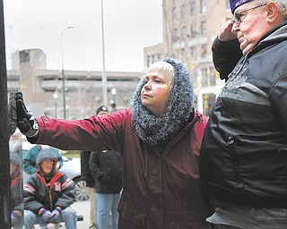 Community members honored their loved ones who sacrificed their lives to the Vietnam War at the 21st annual Laying of the Roses ceremony in downtown Youngstown on Sunday. Above, Kathy Rose and Clint Ray of Austintown honor their loved one, Charles Brown Jr., at the war memorial on Central Square.