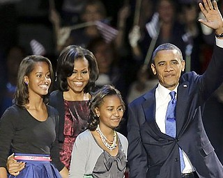 President Barack Obama waves as he walks on stage with first lady Michelle Obama and daughters Malia and Sasha at his election night party Wednesday night in Chicago after defeating Republican challenger former Massachusetts Gov. Mitt Romney.