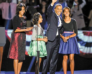 President Barack Obama waves as he walks on stage with first lady Michelle Obama and daughters Malia and Sasha at his election night party in Chicago.