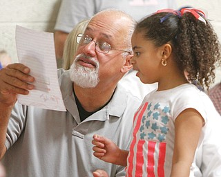 Ralph Santos, a veteran who served four years in the Navy aboard the carrier JFK, reads a thank-you note from Victoria King, a second-grader at Stadium Drive Elementary School in Boardman. More than 100 veterans attended the event Thursday.