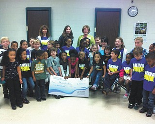 Home Savings Charitable Foundation recently donated a check for $5,000 to Akiva Academy in Youngstown to help the school to continue offering learning programs to an ever-widening range of students. Last year 100 percent of Akiva's third- graders scored proficient or higher on the reading and math Ohio Achievement Tests. Students at Akiva enjoyed an educational visit from Home Savings. Adults, standing from left, are Tirtza Kohan, first-grade teacher and Judaic studies coordinator at Akiva; Rachel Smith, customer service representative of Home Savings Liberty office; and Kim Gennaro, branch manager of Home Savings Liberty office.