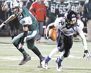 Youngstown Christian's Darrien Townsend (2) keeps his balance after being hit by Malvern's Nick Mohr (1) during the second quarter of Friday night's Division VI regional semifinal at Akron St. Vincent St. Mary High School in Akron. YCS won, 25-20.