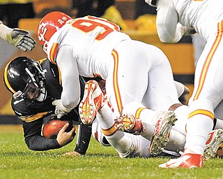 The Kansas City Chiefs' Tamba Hali (91) assists as teammate Justin Houston (bottom of pile) sacks Pittsburgh