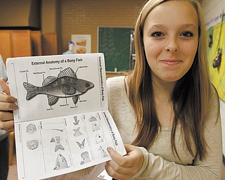 Maddi Graham, an eighth-grader at Akiva Academy in Youngstown, shows a project book she and her classmates used during a visit last month to the Stone Laboratory, The Ohio State University's island campus on Lake Erie.