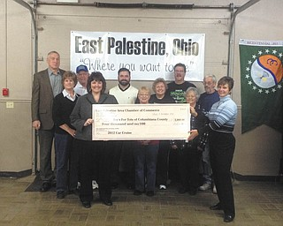 East Palestine Area Chamber of Commerce presented a check for $4,000 to Deb Oberlin of Toys for Tots of Columbiana County Nov. 1 at the East Palestine Community Center. The check represents proceeds from the 14th Annual Toys for Tots Car Cruise. Approximately $3,000 worth of toys also were donated during the cruise. Pictured are some members of the Chamber of Commerce and Nostalgia Haulers Truck Club who sponsored the cruise for 13 years and who volunteered at this year's cruise. Holding the check are Deb Oberlin and Kerri Stewart. In second row from left are Sandy Wales, Margo Zuch, Trudy Barton and Sandy Elis. In back are Don Elzer, Larry Wales, Pete Monteleone, Village Manager; John Barton and Bob Elis.