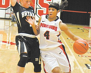 Youngstown State freshman guard Shar'Rae Davis (4) drives around Bryant's Katie Whittington (11) during the first half of a game Sunday at Beeghly Center. Davis scored 23 points and had five steals and four assists in the Penguins' 75-59 victory. The YSU women's basketball team is off to a 3-0 start.