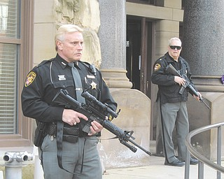 Lt. Pete Lucic, left, and Maj. Harold Firster of the Trumbull County Sheriff's Office stand guard in front of the county courthouse Monday afternoon. They were preparing for two men to appear for their first hearing in the Nov. 11 shooting death of Marco Dukes, 32.