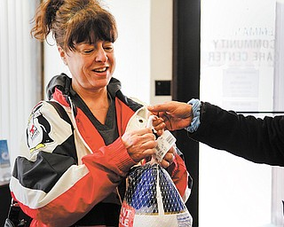 Laura MacGregor of Girard receives a turkey from the Emmanuel Community Care Center in Girard. The center handed out nearly 400 holiday baskets Tuesday to families in Girard, McDonald and Mineral Ridge. Along with turkeys, the center offered bags full of potatoes, bread, pumpkin pie, green beans, cranberries and milk.