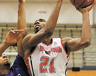 Youngstown State's Damian Eargle (21) puts in a layup to reach 1,000 points for his career with the Penguins as James Madison's Enoch Hood (1) defends during the second half of Tuesday's game at Duquesne University's Palumbo Center. Eargle finished the game with 17 points, six rebounds and six blocked shots in YSU's 69-68 loss.