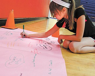 Austintown Middle School students are talking about their families' struggles with various types of cancer. Here, Devyn Coast signs a paper with the names of people in her family.