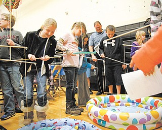Fifth-grade students at Springfield Intermediate School catch numbered fish with magnetic poles from inflatable kiddie pools, then calculate the mean, median and mode of numbers. The activity was part of a camping-themed Math Night on Thursday in the school gym.