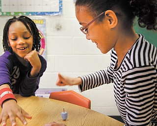 "Manny Rivera, left and Kayla Paez, first-graders at Akiva Academy in Youngstown, spin dreidels in their classroom. The students will participate in ""Light,"" a community Hanukkah program Thursday."