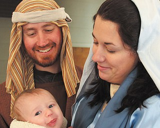 Evan Grope is all smiles in his role as baby Jesus as his parents, Michael and Sarah Grope, share the happy