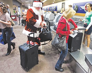 Holiday travelers, including Santa Claus, check in with customer service agent Angelee Arciniega, right, for their Southwest Airlines flight at Sky Harbor International Airport in Phoenix. Thousands passed through the airport, many on their way home for Christmas. This year looks to be a busy holiday travel year, especially on the roads.